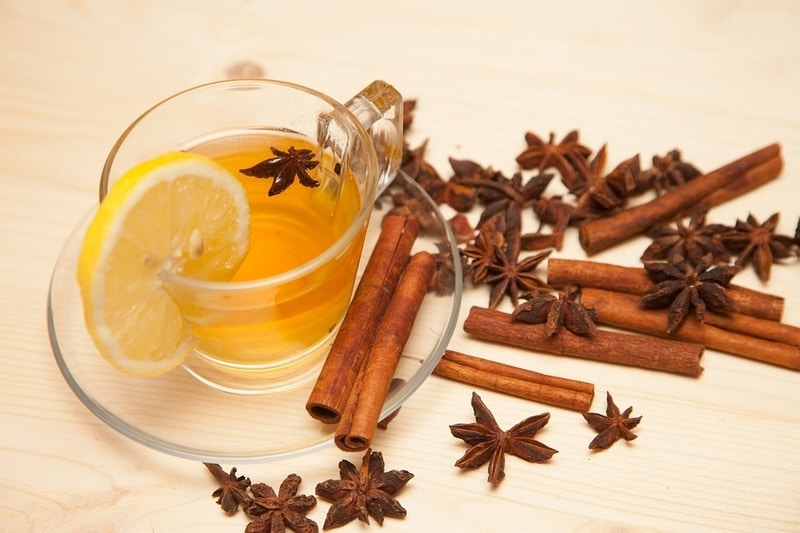 Star anise tea in a cup with star anise pods and cinnamon sticks arrayed around it