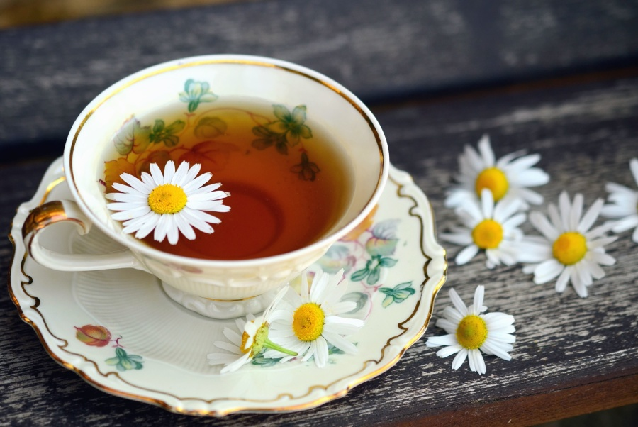 Chamomile tea in an elegant teacup. Chamomile flowers float on the tea and rest around it.