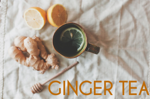 Ginger tea with sliced lemon, ginger root, and honey wand surrounding it. All ingredients are laid out on a white cloth background.