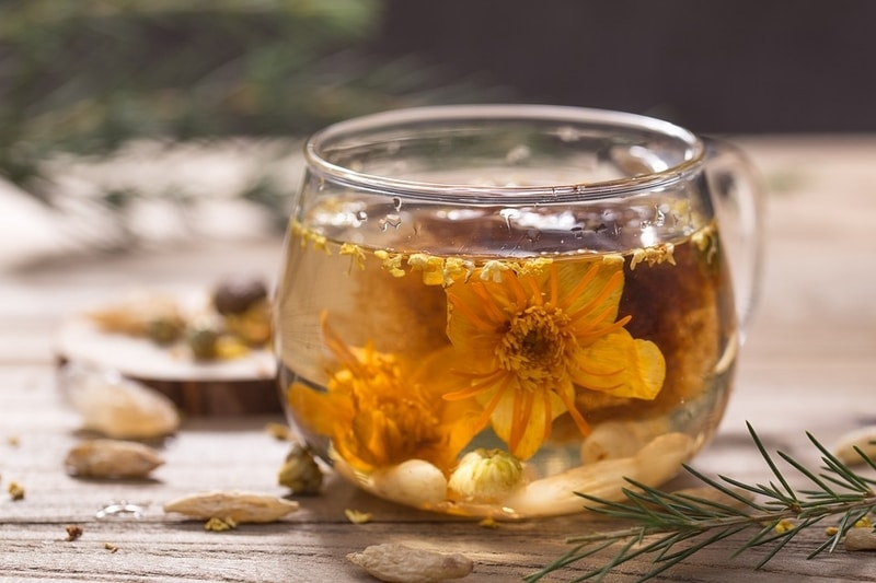 Glass of herbal tea containing a suspended flower. Bits of herbs and flowers surround the glass.