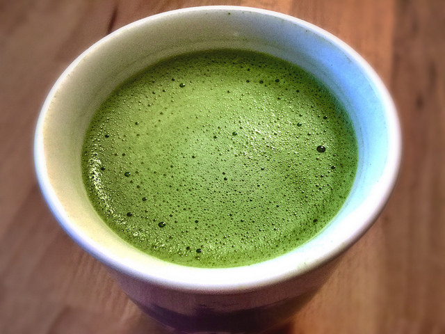 A downward look into a cup of frothy matcha green tea