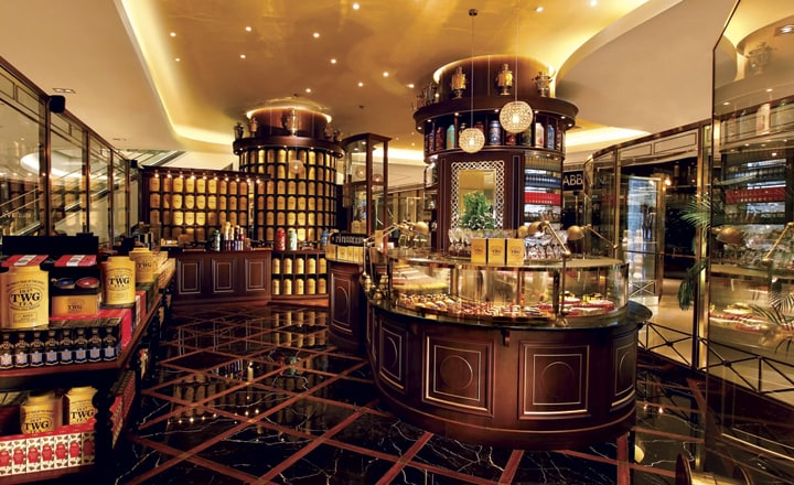 The view inside a TWG tea shop. The design is very luxurious with dim lightning and black floor tiles. Different teas are out on display.